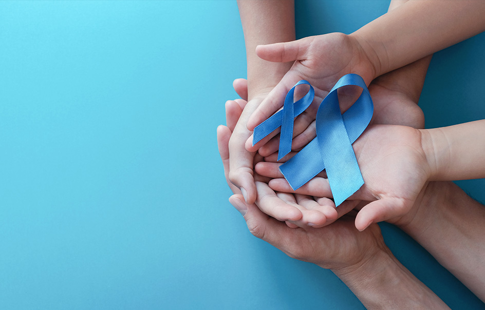 A group of hands holding two blue awareness ribbons