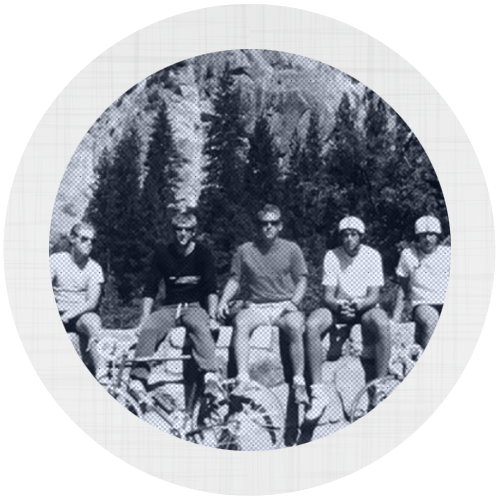 A group of men sitting on a stone wall with their bicycles