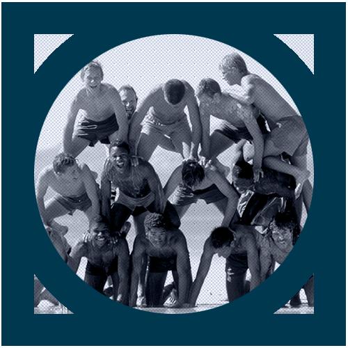A group of teens making a human pyramid